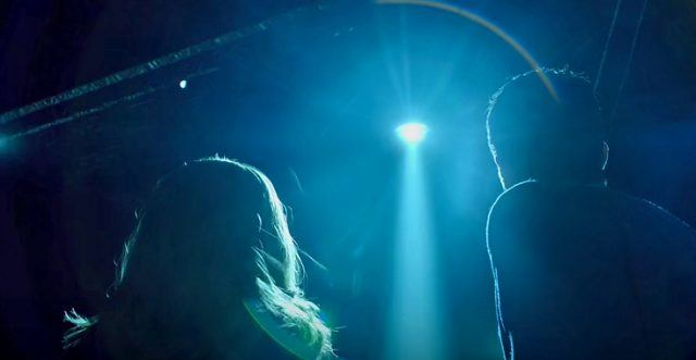 Scully and Mulder stare up at the sky as a light beams down in a scene from the 'X-Files' Season 10 finale.