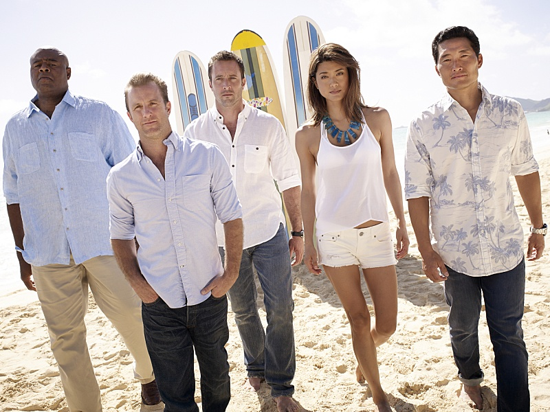 The cast of Hawaii Five-O walks on a beach with surfboards and the ocean in the background
