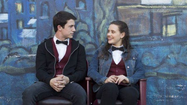Clay and Hannah wear their movie theater uniforms and sit outside, talking, in a scene from '13 Reasons Why.'