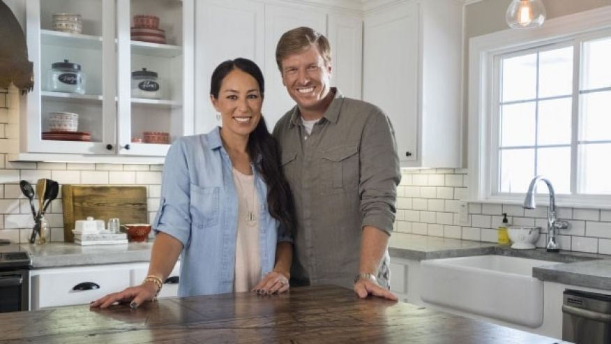 Chip and Joanna Gaines stand at a table in HGTV's Fixer Upper