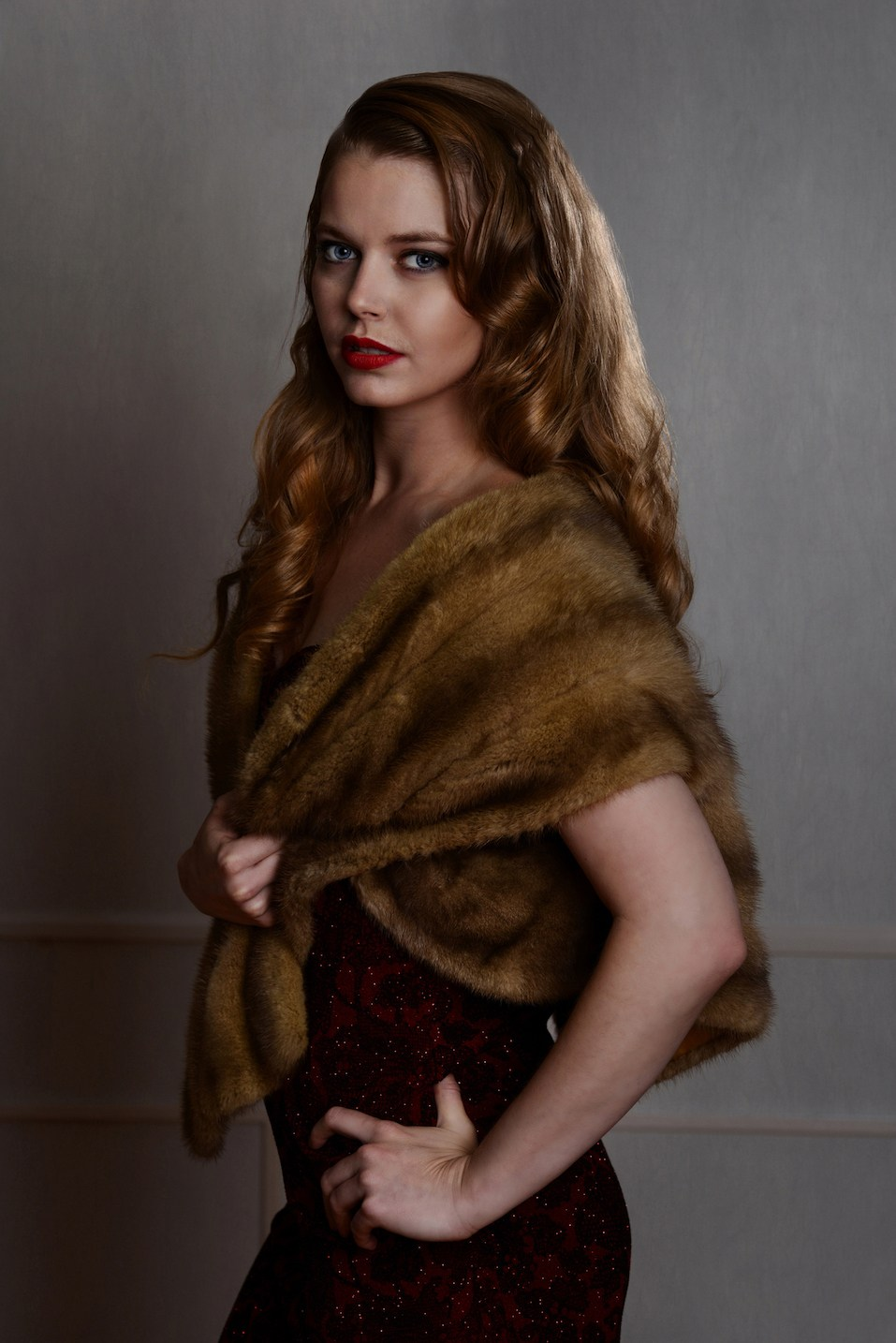 1940s glamour portrait wearing fur wrap with hand on hip