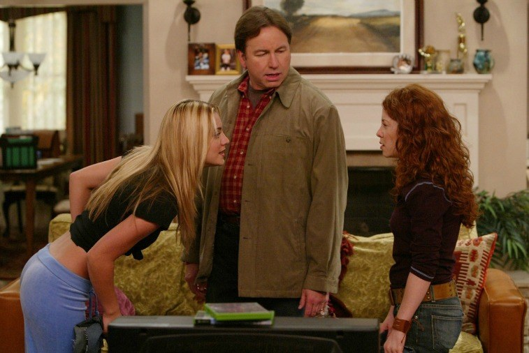 Kaley Cuoco stares angrily at Amy Davidson while John Ritter looks on in a living room set for 8 Simple Rules