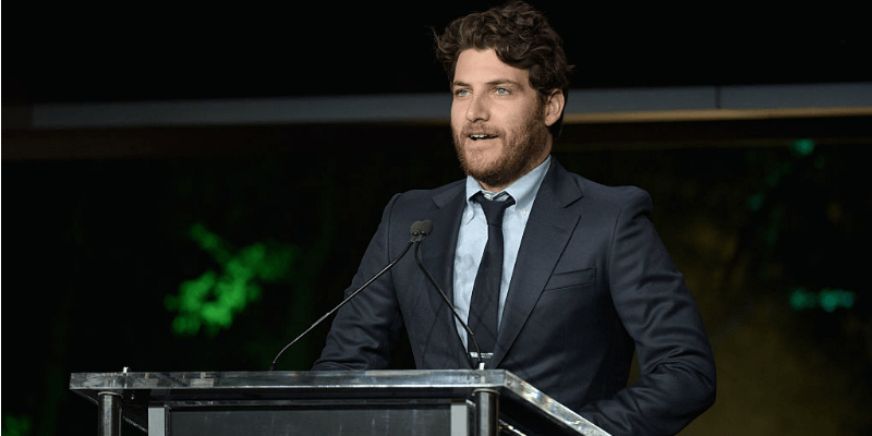 Adam Pally is talking on stage at a podium.