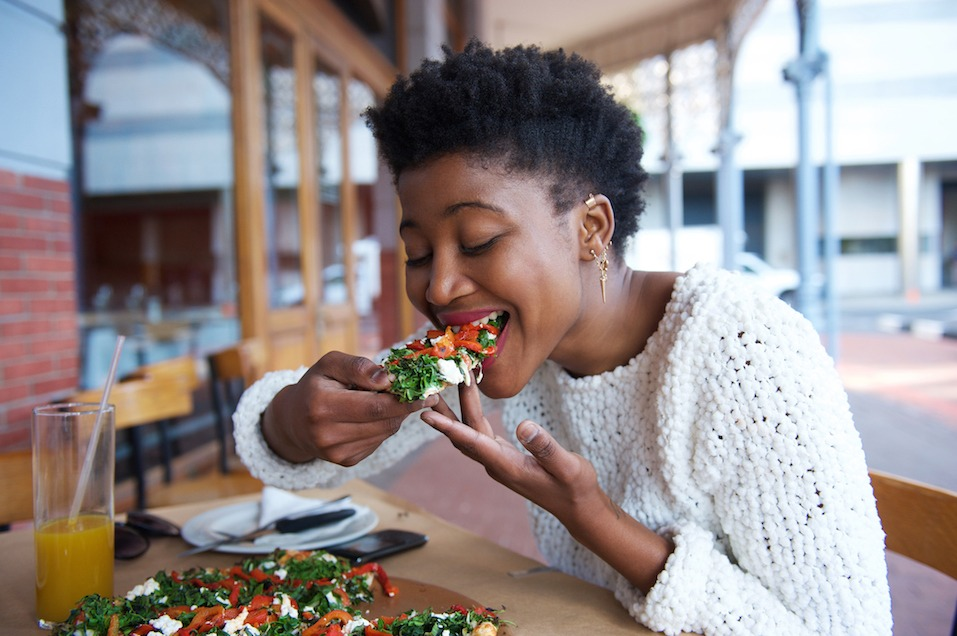 African american woman eating pizza