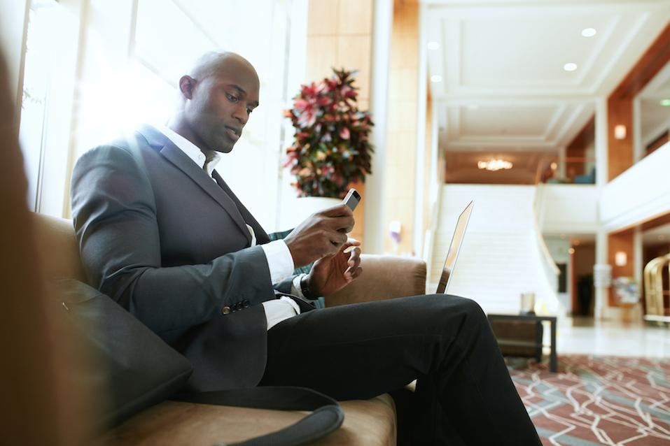 Male executive sitting on sofa looking at his mobile phone