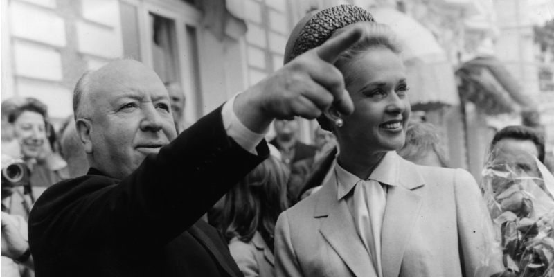 Alfred Hitchcock is pointing into a crowd and Tippi Hedren is smiling next to him.