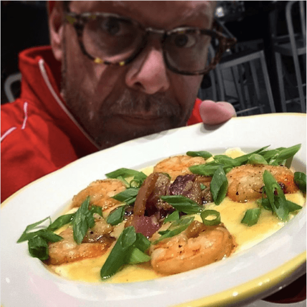 Alton Brown holds up a plate of food