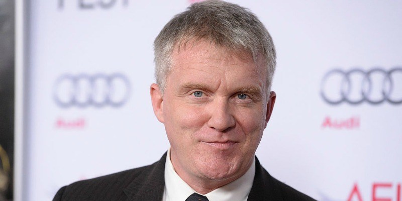Anthony Michael Hall is smiling in a suit on the red carpet.