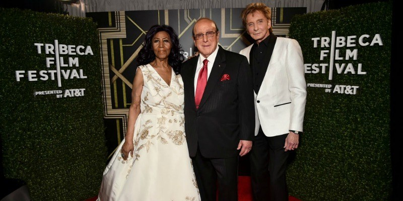 Aretha Franklin poses in a while gown with Clive Davis and Barry Manilow.