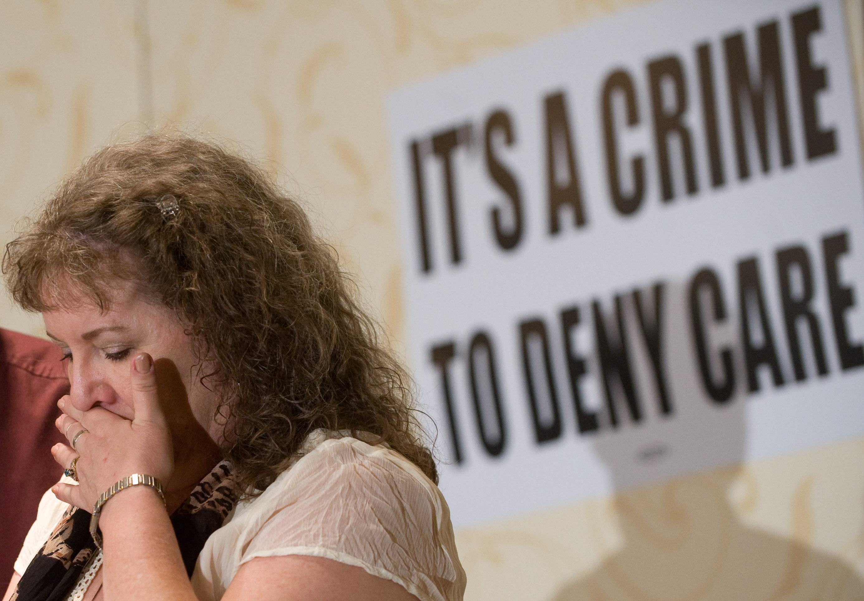 "Kelly Arellanes of Little Rock, Arkansas, cries in front of a sign that says ""it's a crime to deny care"""