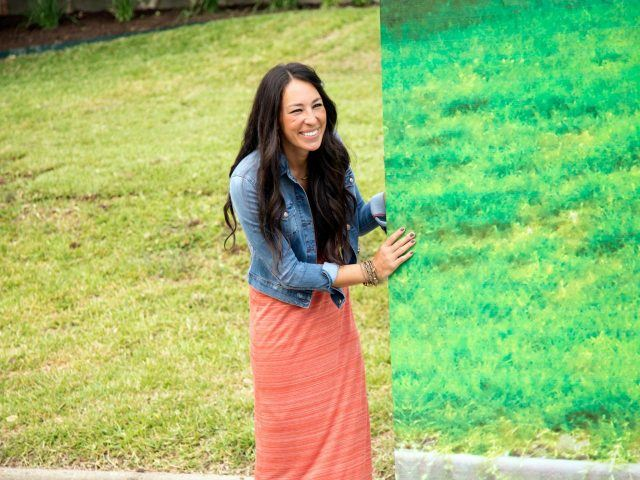 Joanna Gaines carries a banner outside on a lawn.