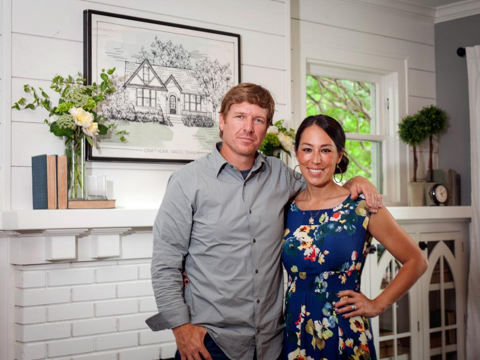 Chip and Joanna Gaines stand in front of a mantle