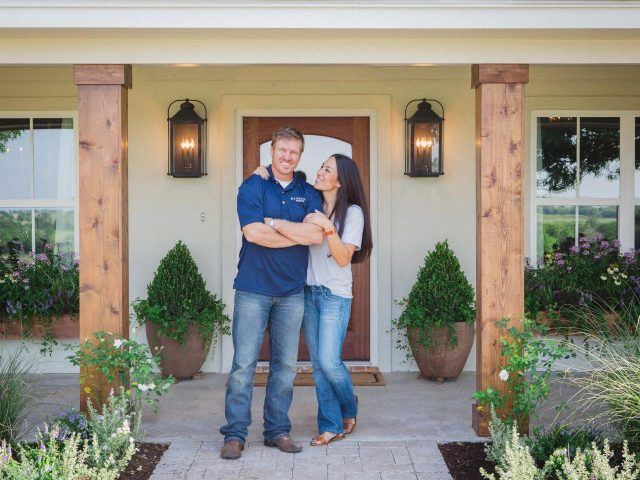 Chip and Joanna stand in front of a house while smiling and laughing.