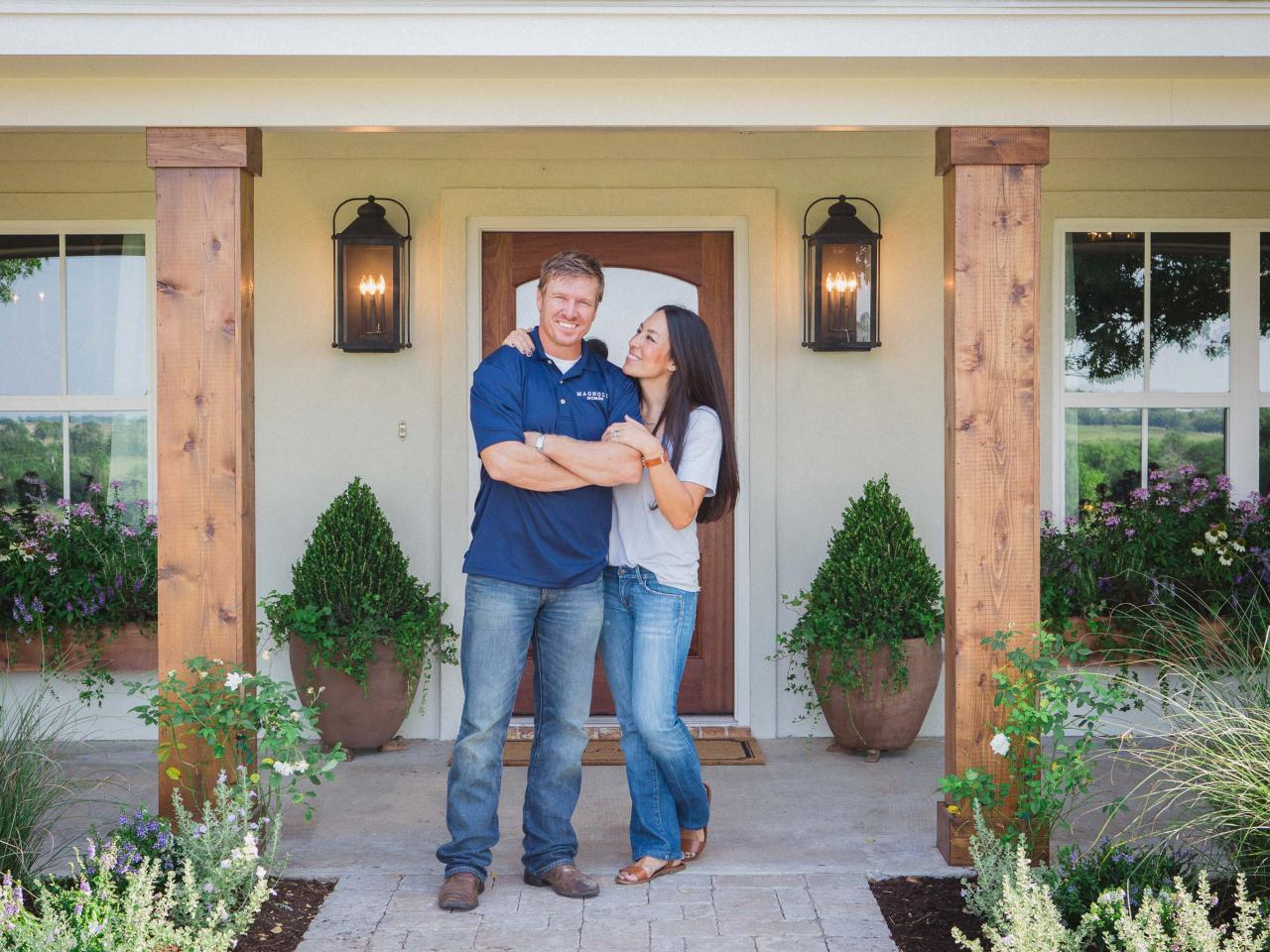 Chip and Joanna Gaines pose in front of a house in Fixer Upper