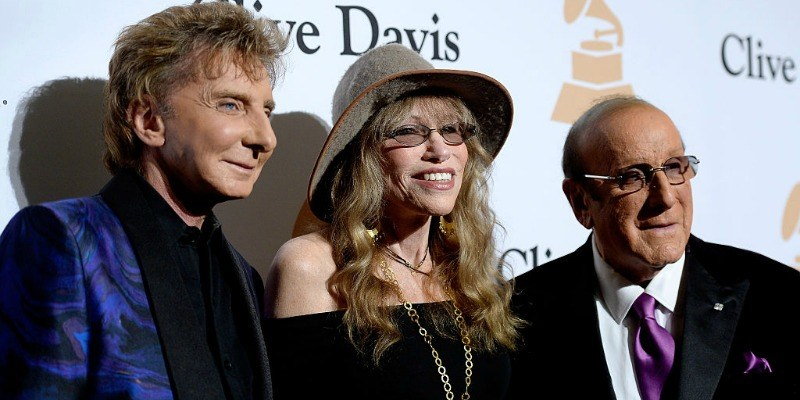 Barry Manilow, Carly Simon, and Clive Davis pose on the red carpet together.