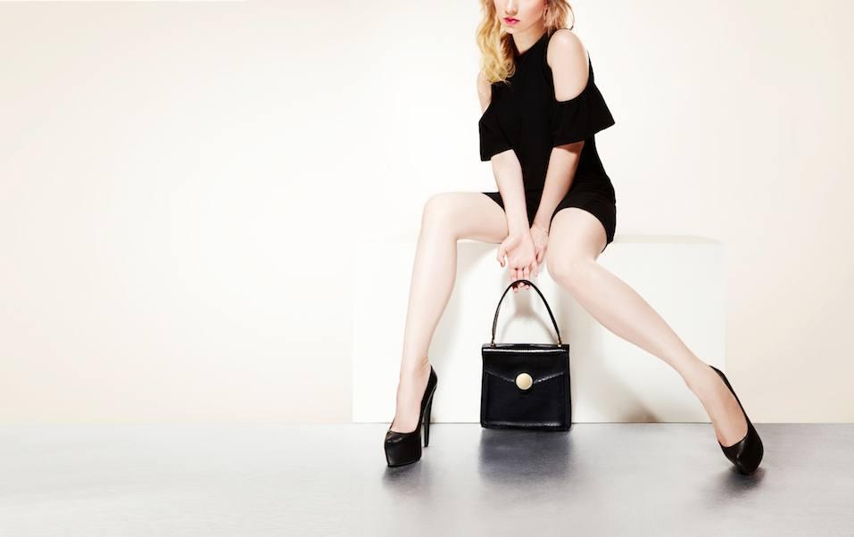 Beautiful Lady sitting holding black hangbag