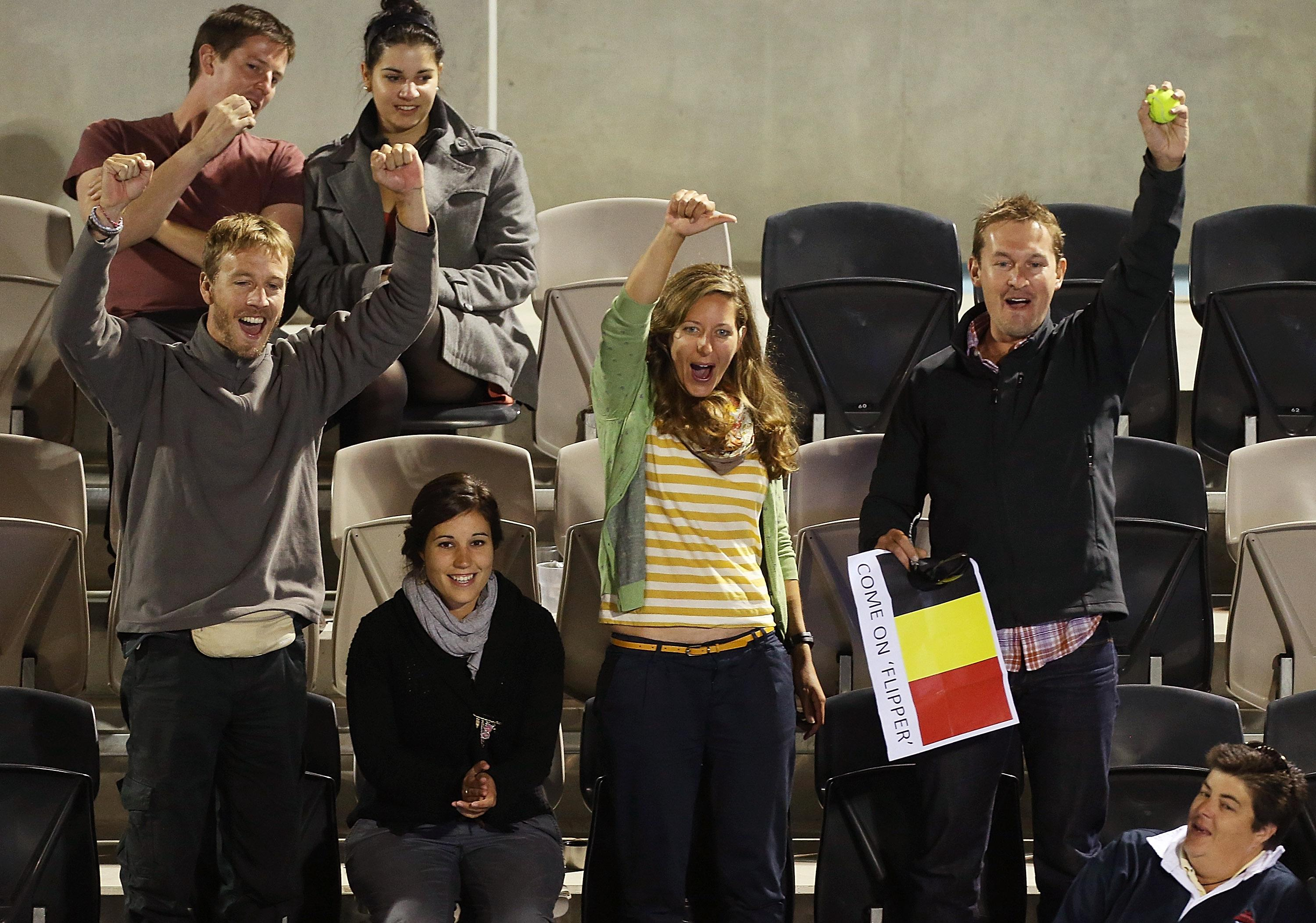 Fans with a Belgium flag cheer at a tennis match