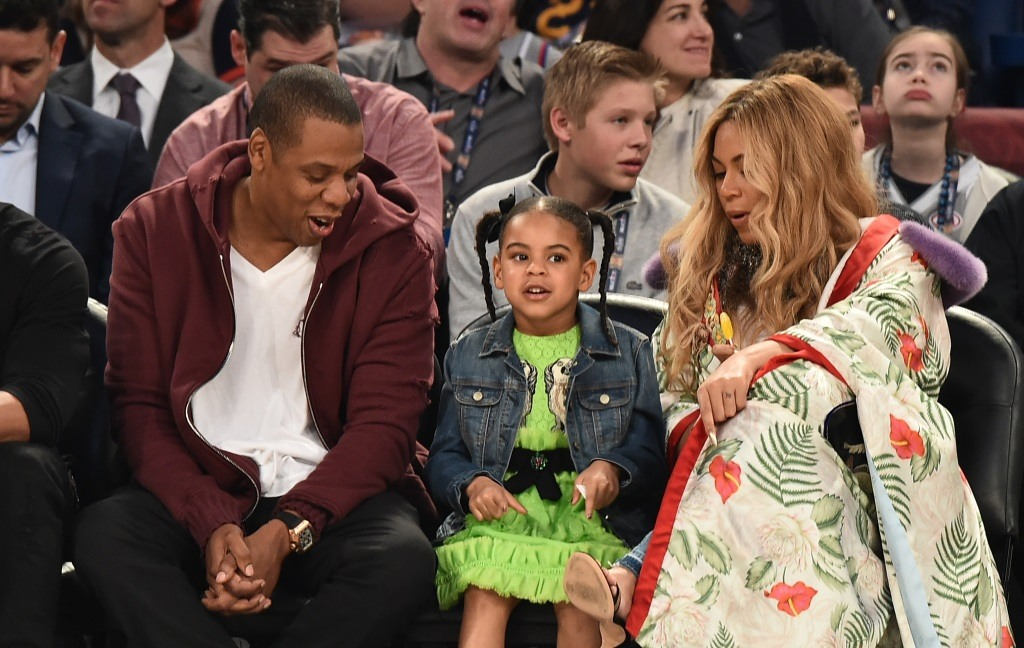 JAY-Z, Blue Ivy Carter, and Beyoncé Knowles sit court side at an NBA basketball game