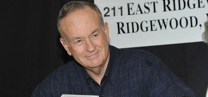 Bill O' Reilly is smiling while he is signing books.