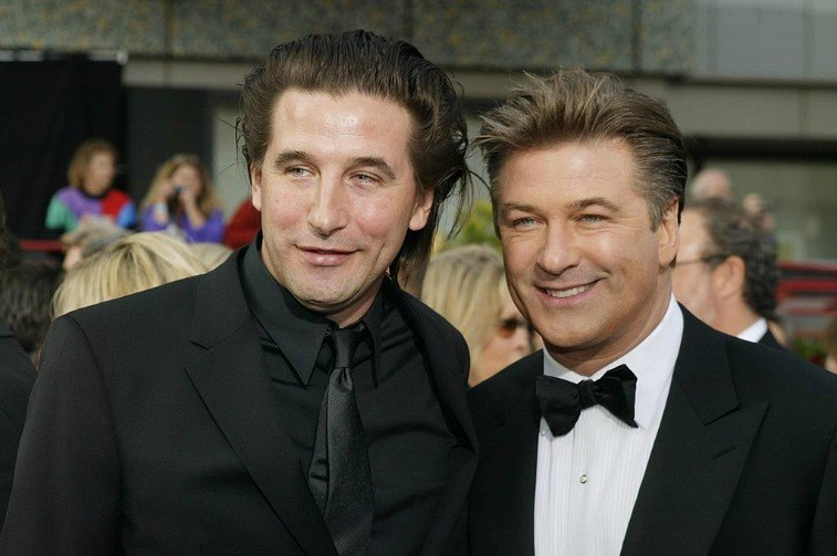 Brothers Billy Baldwin and Alec Baldwin in suits smiling for the paparazzi