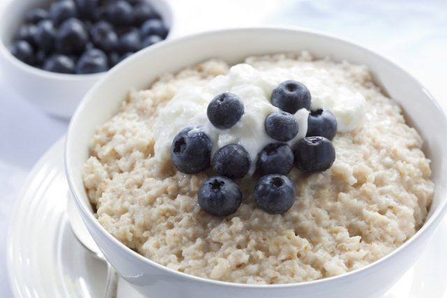 Bowl of oatmeal porridge, topped with fresh blueberries and yogurt