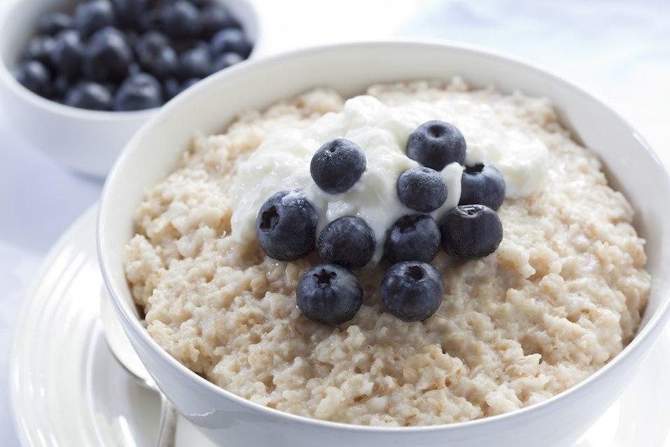 Bowl of oatmeal porridge, topped with fresh blueberries and yogurt