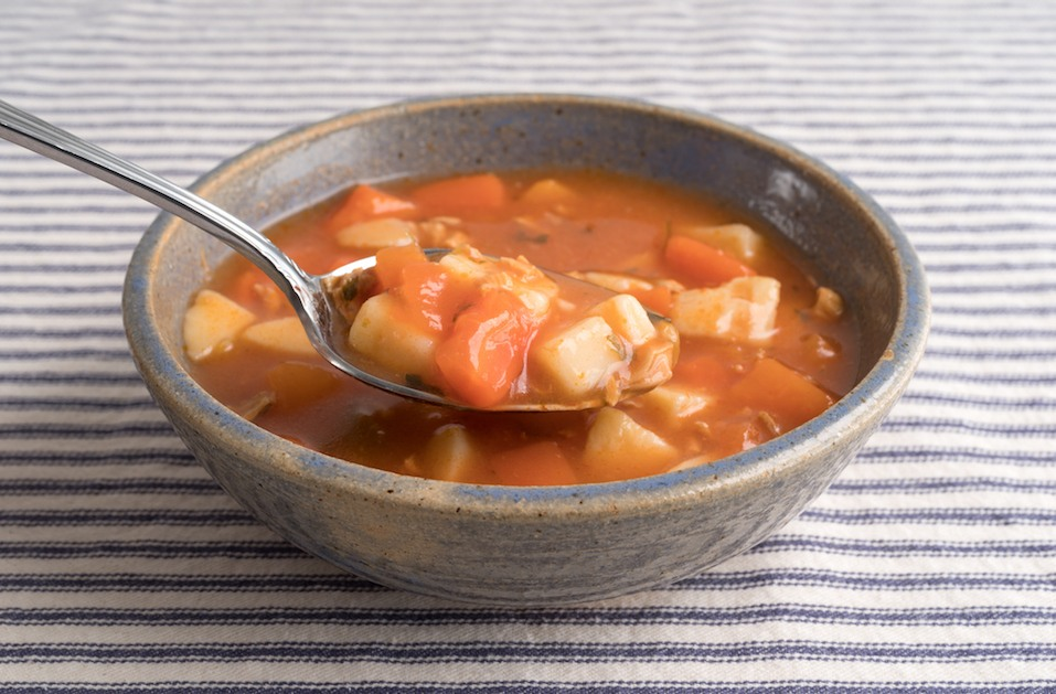 Bowl of Manhattan style clam chowder with spoonful