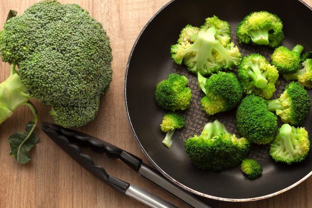 Broccoli in pan on wood kitchen table