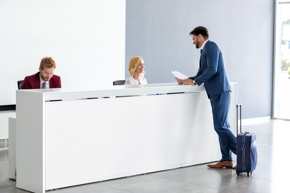a businessman talking to a receptionist