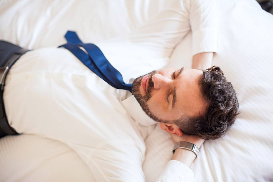 Handsome young businessman lying on a bed in a hotel and relaxing