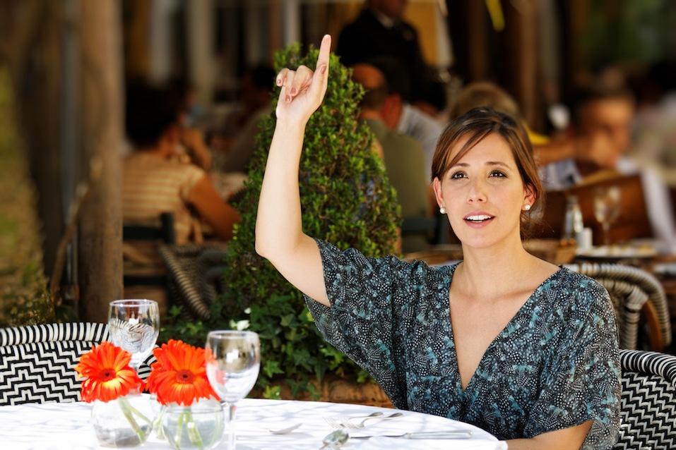 Woman signals the waitress