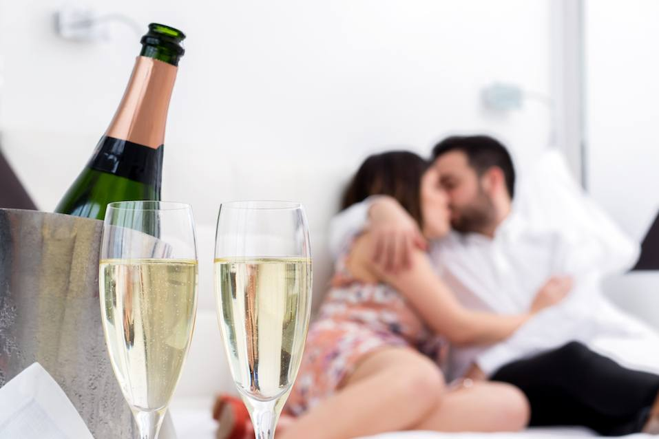Champagne glasses and cold bottle in ice bucket with kissing couple in background