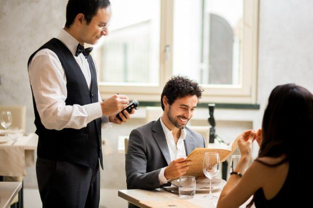 A server takes an order from a couple.