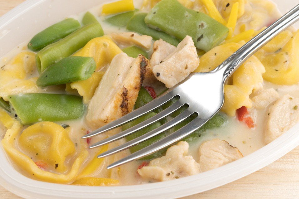 Chicken with tortellini and vegetable TV dinner in a plastic tray with a fork atop a wood table.