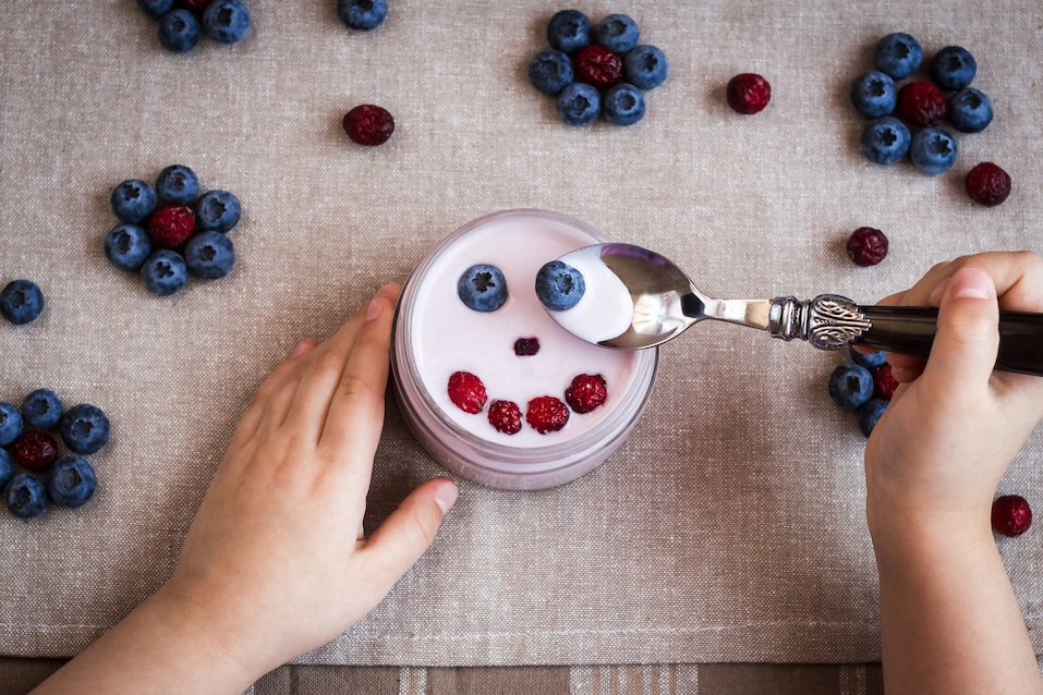 Child hold a spoon with yoghurt and blackberry