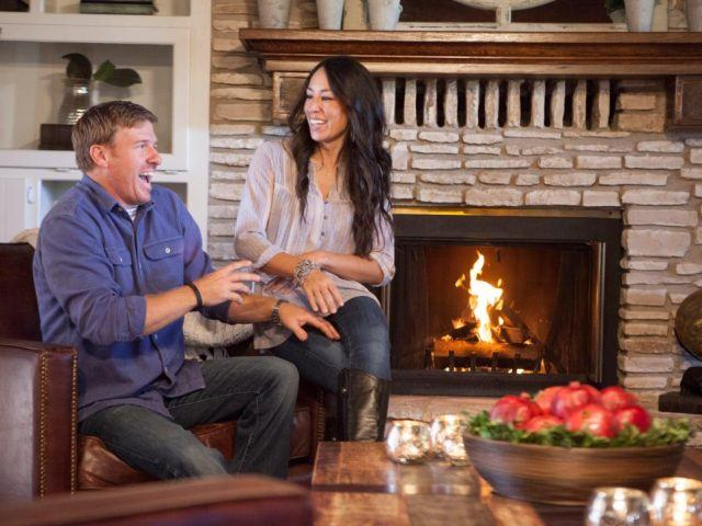 Chip and Joanna Gaines sitting on a chair in front of a fireplace.