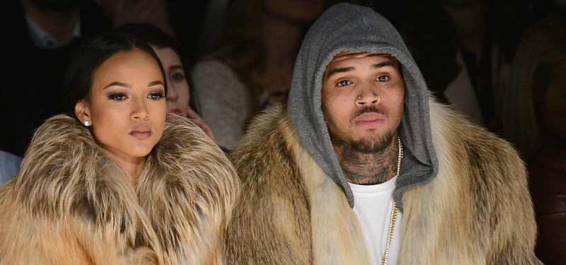 Karreuche Tran and Chris Brown are sitting down front row at a fashion show in fur coats.