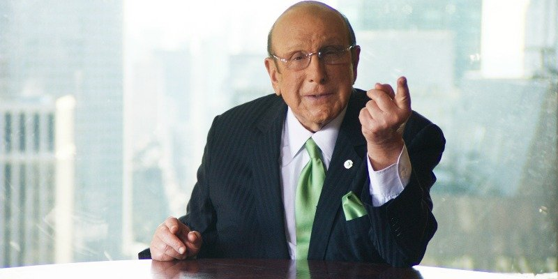 Clive Davis is talking and pointing while sitting down at a desk.