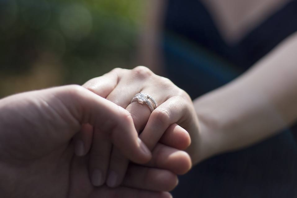 holding hands with wedding ring