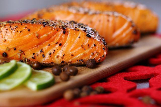 Grilled salmon with lime on a wooden board.