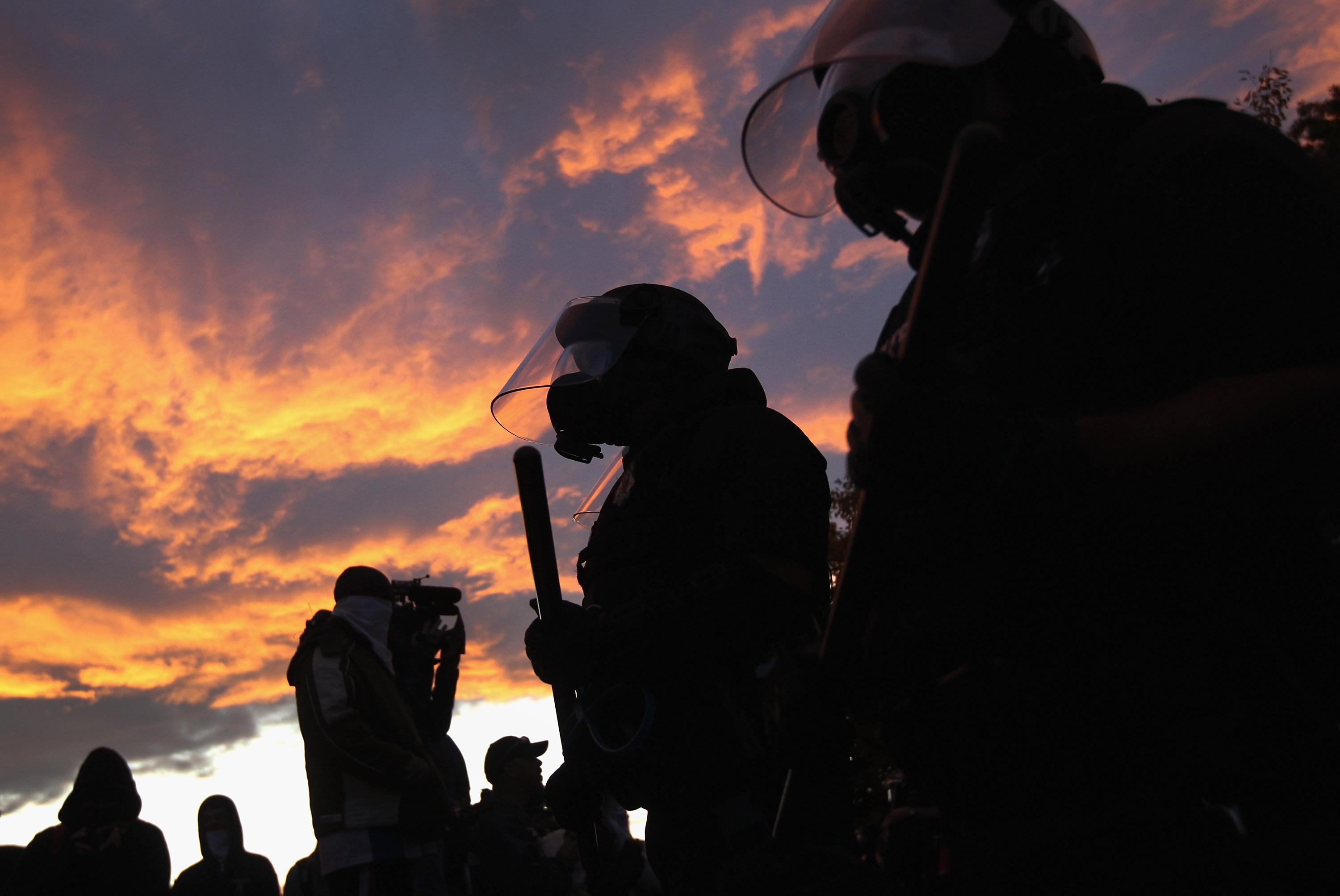 """Riot police face off with demonstrators at the """"Occupy Denver"""" camp"""