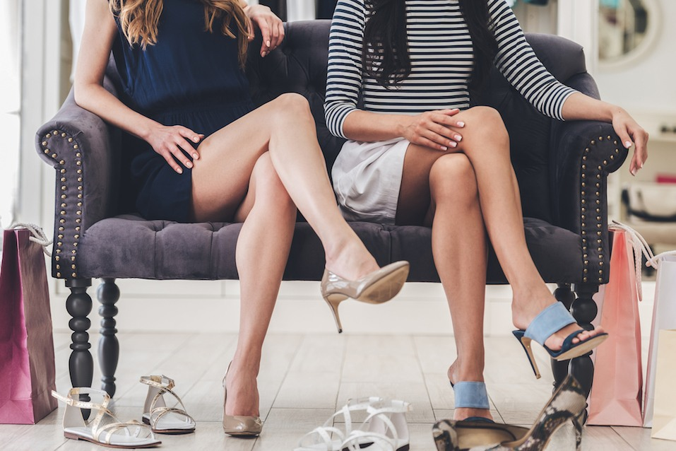 young women with perfect legs keeping their legs crossed at knee while sitting on sofa at the shoe store