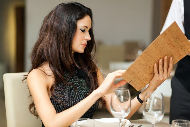A woman looks at a menu.
