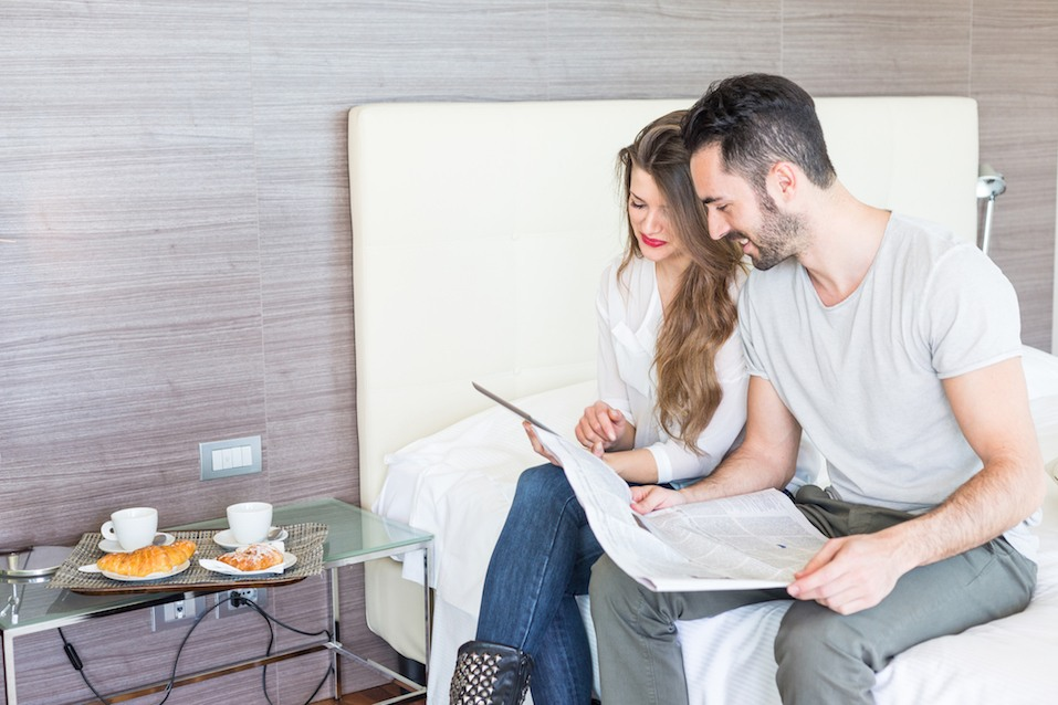 Couple with newspaper and tablet on a bed