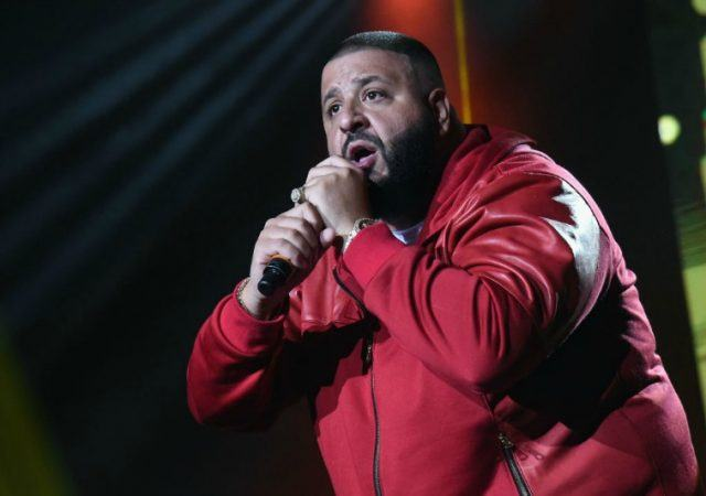 DJ Khaled holds a microphone while performing on stage.