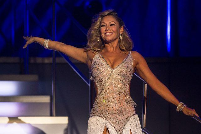 Kym Johnson strikes a pose in a glittery dress.