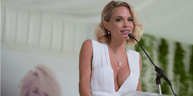 Dani Mathers is on stage in a white dress at a podium.