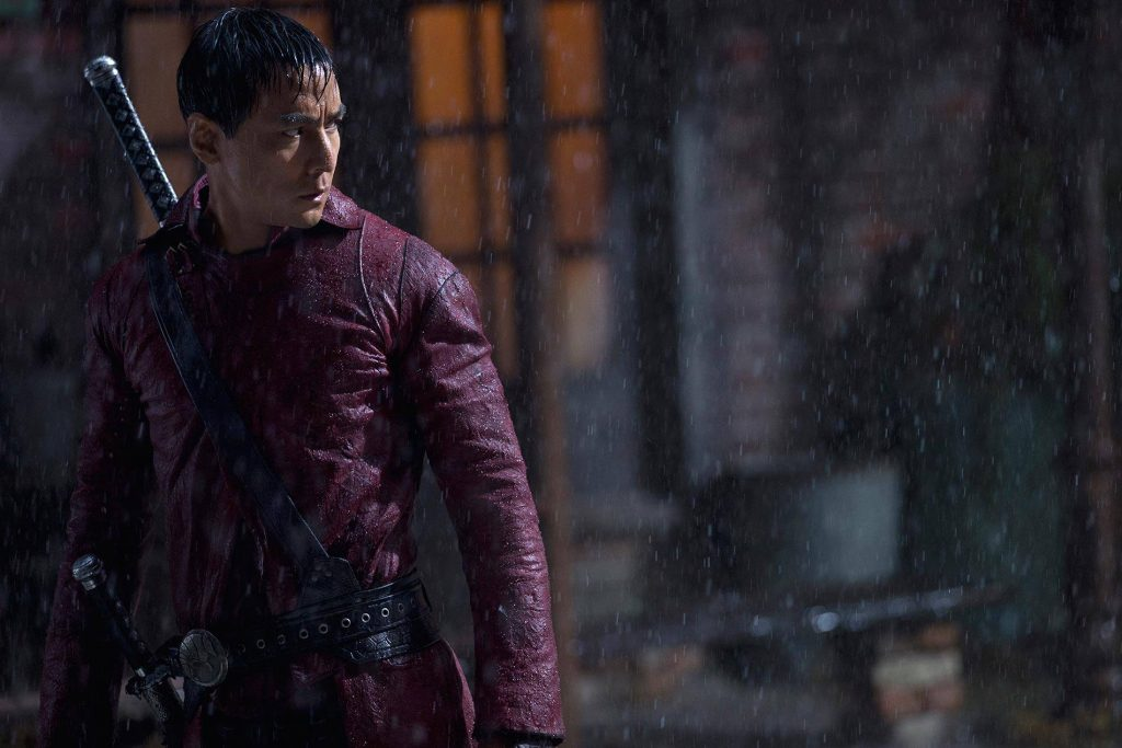 Daneil Wu in a red leather jacket, with a sword strapped across his back