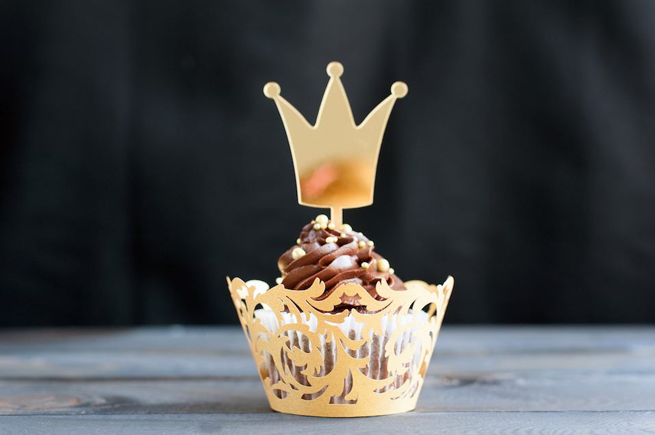 Cupcakes with chocolate cream and topper in the shape of a gold crown
