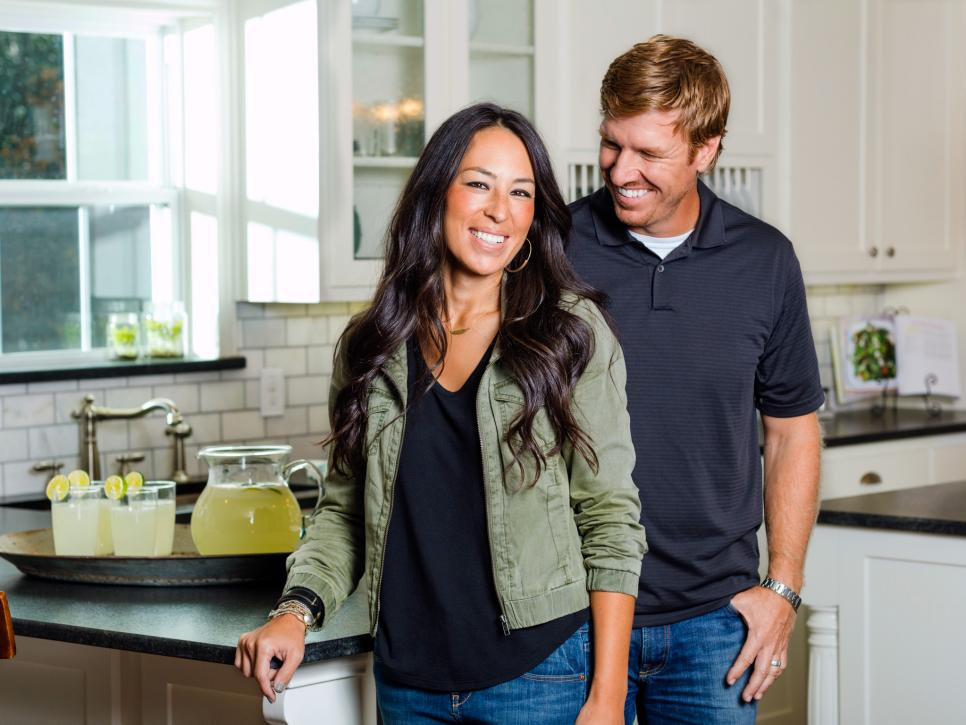 Designers Chip and Joanna Gaines pose in a kitchen in front of a platter with a pitcher of lemonade on HGTV's Fixer Upper.